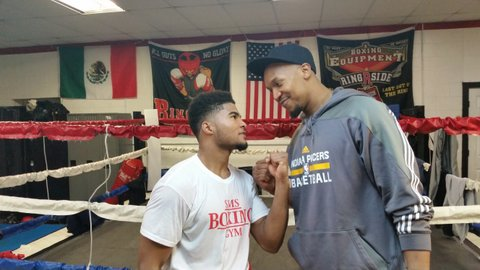 Local boxer Anthony Sims at his gym, mugging with David West.